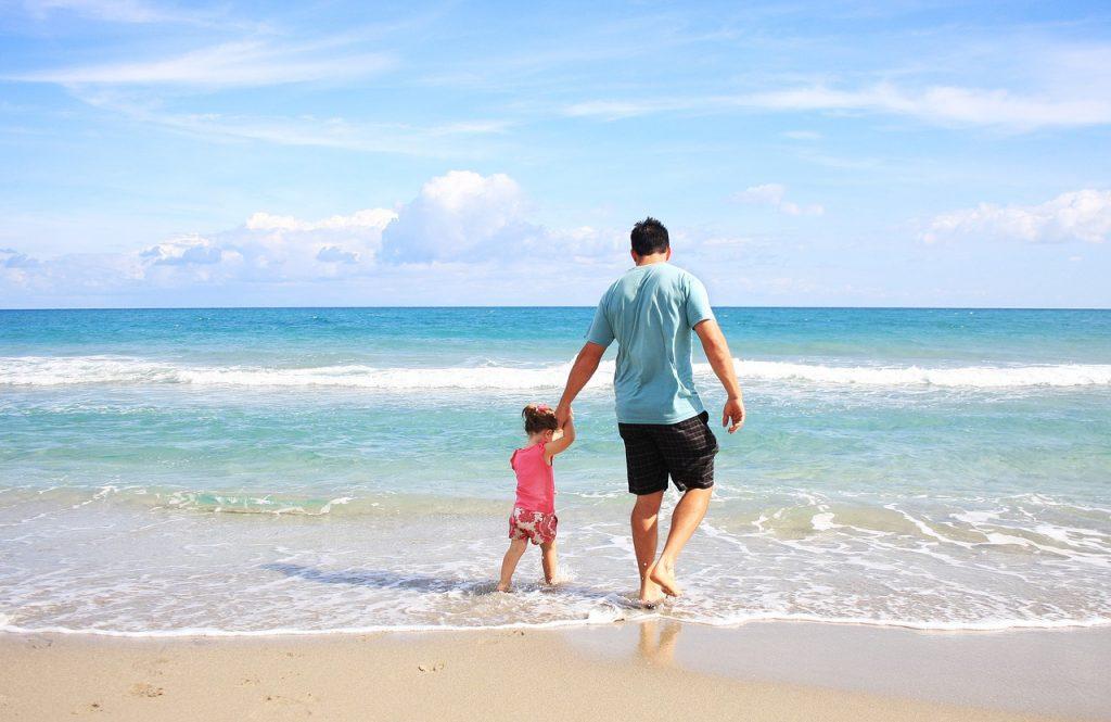 Папа в день рождения гуляет с дочкой по пляжу