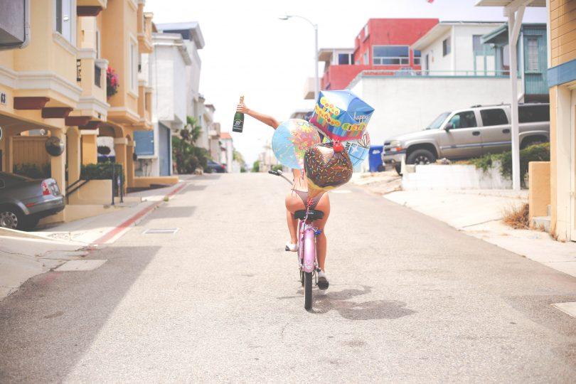 Девушка с шариками на велосипеде в день рождения
