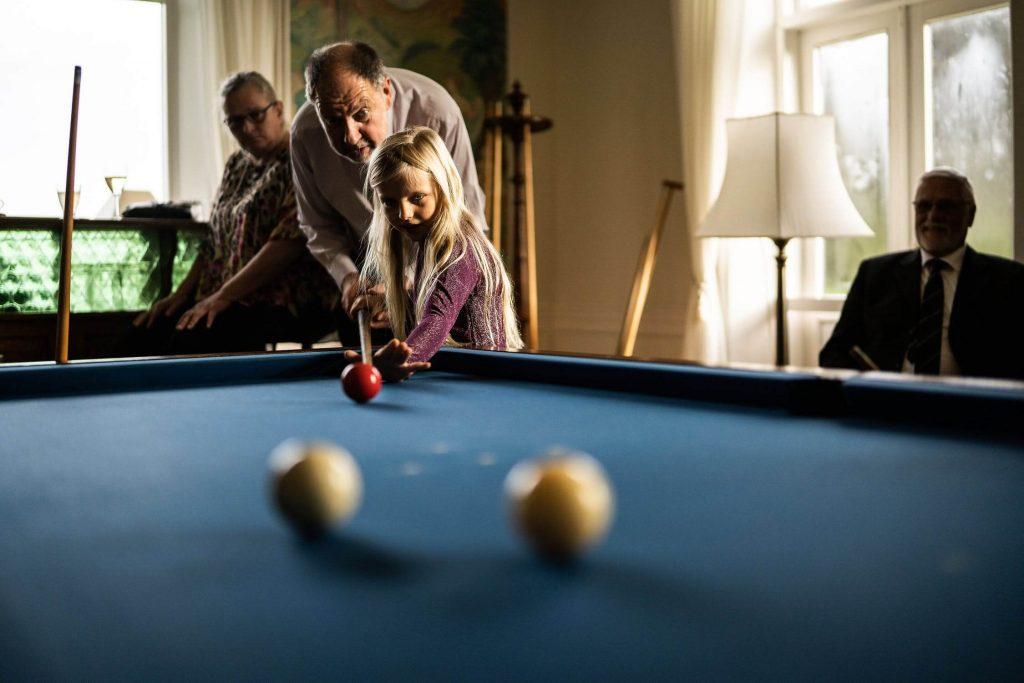 Дедушка и внучка играют в бильярд