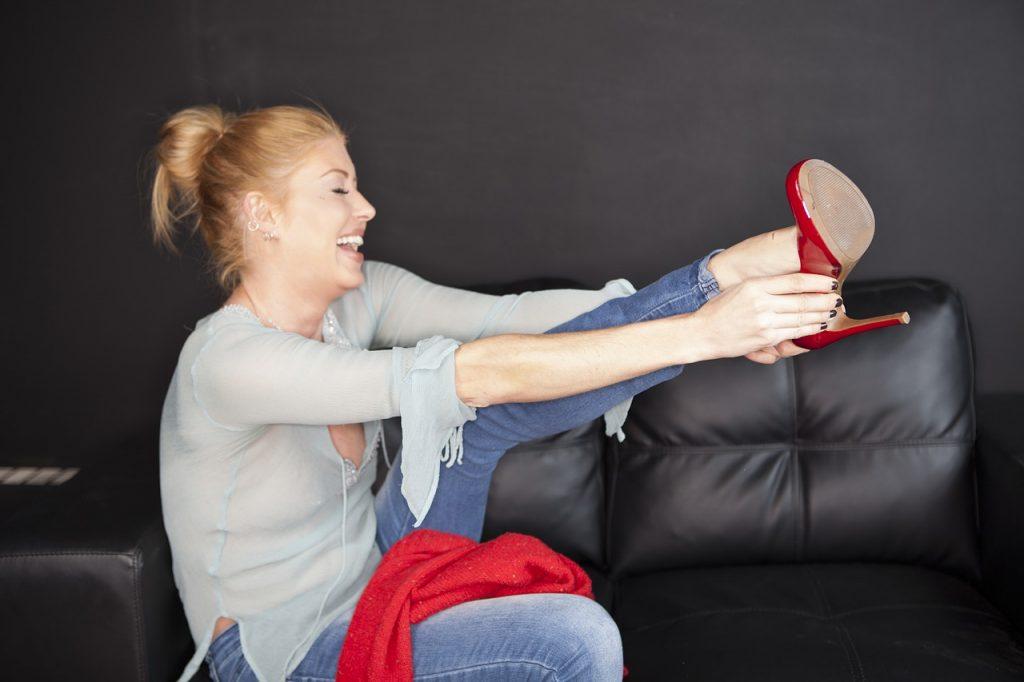 Веселая женщина одевает каблуки